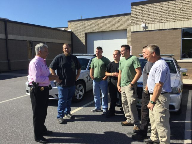 Sheriff Chris Bowman (left) briefs the group before his deputies depart for Robeson County, NC.