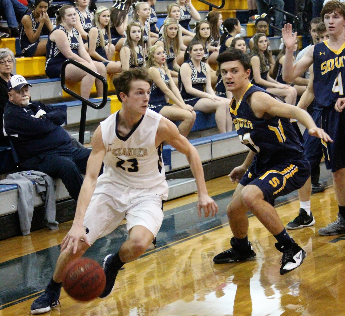 Junior guard dribbles past a South Iredell defensive player
