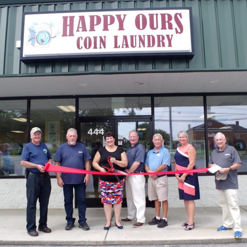 NEW LAUDROMAT OPENS — The Happy Ours Coin Laundry opened July 25 at 444 West Main Avenue in Taylorsville. A ribbon cutting was held there Monday, August 10. Shown above, left to right: Town Councilmen Ronnie Robinette and Jack Simms, owners Dana Hopper Baldwin and Tom Baldwin, Councilman Kenny Poole, Councilwoman Kimberly Brown, and Mayor George Holleman.