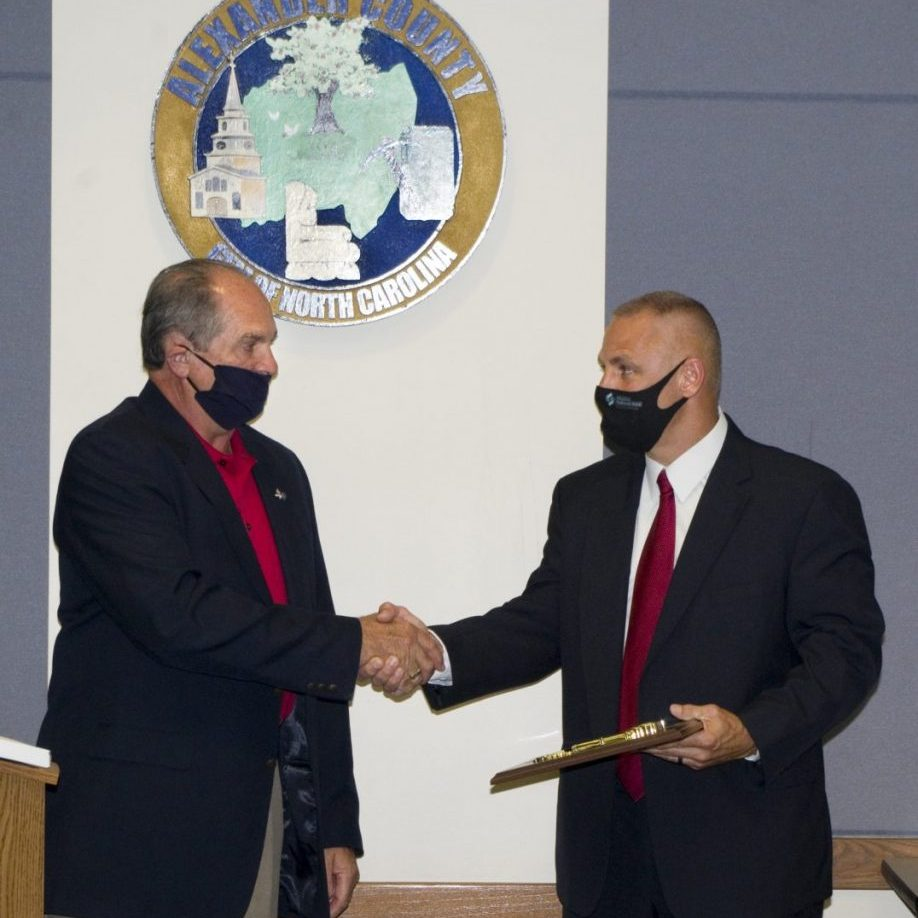 Alexander County Commissioner Ronnie Reese (left) presents the Key to the County plaque to retired Alexander County Sheriff's Office Capt. Chad Pennell at the Commissioners' meeting on Sept. 14, 2020.
