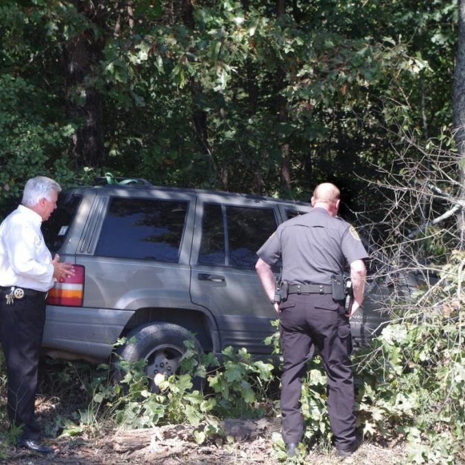 CRASH, SEARCH FOR MOTORIST'S MISSING DOG LEAD TO GRISLY DISCOVERY — After the driver of this Jeep crashed into a tree on County Home Road September 28, first responders and officers arrived. While the motorist's brother stood by to wait on a wrecker and look for the motorist's dog, he discovered a wallet and a deceased man lying nearby. Above, Sheriff Chris Bowman (left) and Maj. Jason Moore investigate the wrecked Jeep.